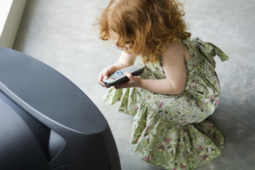 Little girl crouching in front of television, holding remote control, elevated view