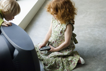 Little girl kneeling in front of television, holding remote control, elevated view