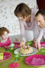 Couple and little girl with birthday cake at lunch table