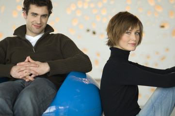 Couple sitting in living-room, looking at the camera