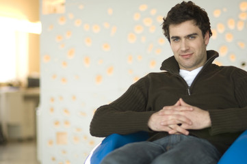 Man sitting in living-room looking at the camera