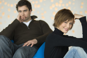 Couple sitting in living-room, woman smiling for the camera, man thinking in the background