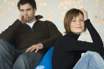 Couple sitting in living-room, woman looking at the camera, man thinking in the background