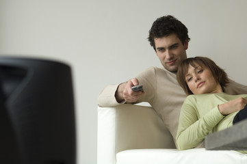Couple lying on a sofa, watching TV