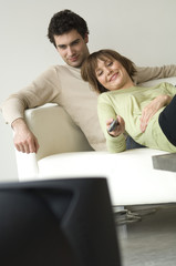 Smiling couple lying on a sofa, watching TV