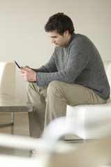 Man sitting on a sofa using a mobile phone