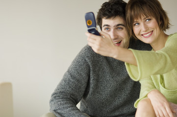 Smiling couple taking picture with camera phone