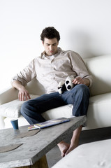 Sad looking man sitting on a sofa, holding stuffed dog
