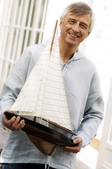 Smiling senior man holding a model boat outdoors
