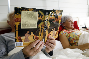 Senior couple in bed, woman sleeping, man reading Kama Sutra book