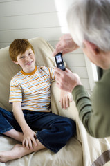 Senior man taking picture of smiling boy with camera phone