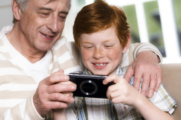 Senior man and boy playing Playstation Portable