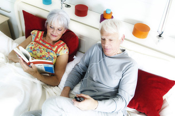 Senior couple in bed, woman reading, man listening to MP3 player, elevated view