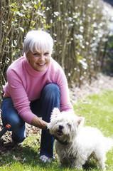 Senior woman crouching, stroking West Highland terrier