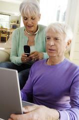 Senior man using laptop computer, senior woman using mobile phone