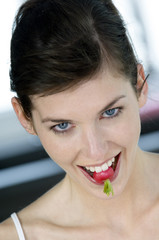 Portrait of a young woman biting into a radish