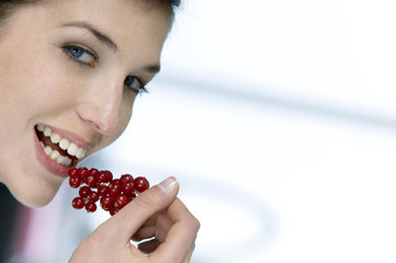 Portrait of a woman eating redcurrants