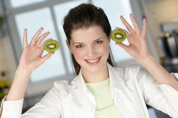 Portrait of a young smiling woman holding 2 halves of kiwi fruit
