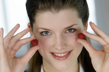 Portrait of a young woman holding 2 raspberries
