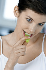 Portrait of a young woman eating apple slice