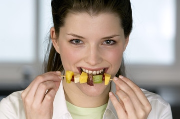 Portrait of a young woman eating a fruit skewer