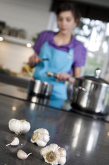 Woman cooking, garlic at the foreground