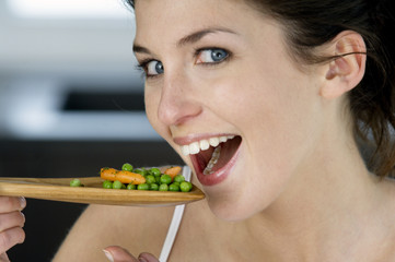 Young smiling woman tasting cooked vegetables