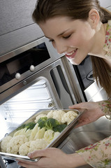 Young smiling woman putting broccolis and cauliflowers into an oven