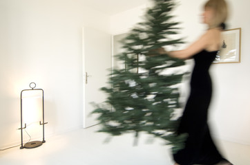 Woman carrying Christmas tree in a living-room