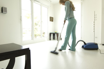 Woman vacuuming in living-room