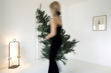Woman carrying Christmas tree in aliving-room