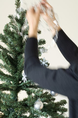 Woman hanging decoration on Christmas tree, close-up
