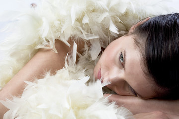 Young woman with white feather boa