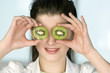 Portrait of a young smiling woman covering her eyes with 2 halves of kiwi fruit
