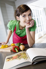 Young woman looking at recipe book, vegetables on a chopping board