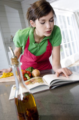 Young woman looking at recipe book, vegetables on a chopping board, chili oil