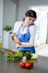 Young woman seasoning a salad