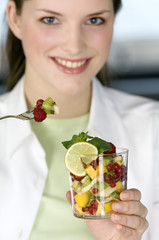Portrait of a young woman eating fruit salad