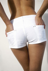 Young woman in shorts, hands in pocket, rear view