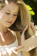 Portrait of a young blond woman brushing her hair, outdoors