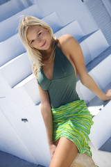 Young smiling woman with pareo and swimming costume, sitting on stairs