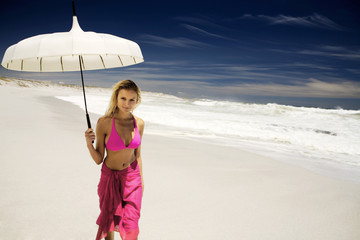 Young woman in bikini and pareo with parasol on the beach