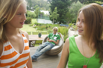 2 teenage girls looking at each other on a terrace, teenage boy sitting in background