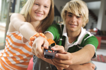 Teenage boy and girl using remote control