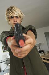 Teenage boy aiming handgun
