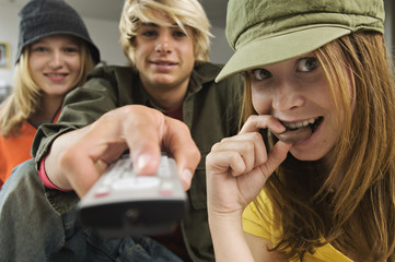 2 teenage girls and teenage boy using remote control
