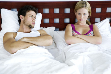 Young couple in bed, arms crossed