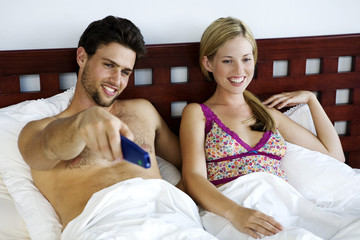 Young smiling couple in bed, watching TV