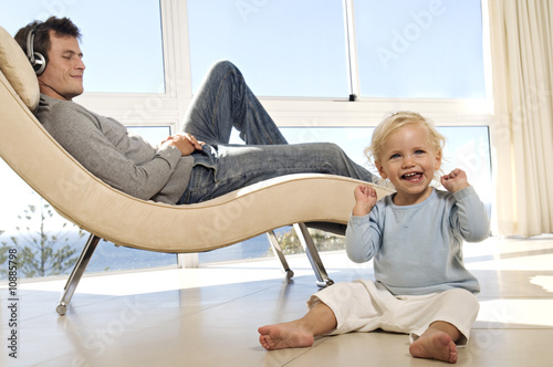 Father and little girl in living room, man listening to music, indoors