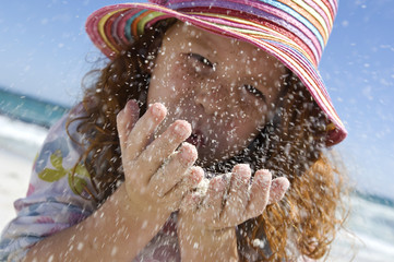 Portrait of a little girl blowing sand in her hands, outdoors